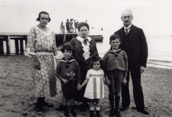 The Hein family, taken at the seashore in 1925.  Dad is the little boy with the pinwheel.  The woman on the left is unknown, probably the governess.